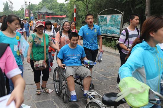 7日下午,一名考生坐着轮椅,被同学推出考场。大众网记者 王传胜 摄.JPG
